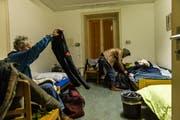 Zwei Obdachlose richten sich in ihrem Zimmer in der Notschlafstelle ein. Hier bekommen sie in den kalten Winternächten ein warmes Bett. (Bild: Roger Gruetter / Neue LZ)