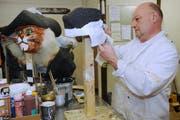 Christoph Koch von der Chatzemusig arbeitet an einer Maske. (Bild Boris Bürgisser/Neue LZ)
