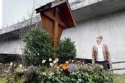 Hildegard Bütler beim Andachtsort unterhalb der neuen Tobelbrücke. Das Kreuz wurde fast durch- gesägt (kleines Bild), die Christusfigur hat Bütler entfernen lassen. (Bilder Werner Schelbert)