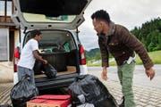 Zügeltag: Die Asylsuchenden Hamdu Kamal (oben links) und Abas Jervar laden in Escholzmatt ihr Gepäck aus. José Flüeler, Vertreter der kantonalen Behörde (Bild unten rechts), übergibt den Männern die Schlüssel. (Bild: Eveline Beerkircher / Neue LZ)