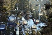 Die Sesselbahn-Cheselen am Donnerstag: Ein Retter naht, Ski- und Snowboardfahrer werden abgeseilt. (Bild: Christoph Riebli)