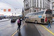 Links: Der Schwanenplatz gestern zur Mittagszeit: An diesem Ort werden Fussgänger häufig durch zu- und wegfahrende Reisecars behindert. (Bild: Roger Gruetter)