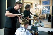 Coiffeur Martin Wunderlin schneidet Nevio behutsam die Haare. Das Tablet hilft dem autistischen Buben, sich zu entspannen. (Bild Corinne Glanzmann)