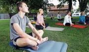 Konzentriert: Autor Nils Rogenmoser bei seiner ersten Yoga-Lektion. (Bild: Werner Schelbert (Zug, 28. Juli 2017))