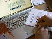 Ein Code für die Abstimmung per E-Voting wird aufgerubbelt (Bild: Keystone)