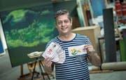 Der Künstler Nils Nova in seinem Atelier in Emmen. In der Hand hält er seine als Kind gezeichneten Schweizer Banknoten. (Bild: Pius Amrein (Emmen, 13. Juli 2017))