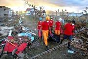 Mitarbeiter des Internationalen Roten Kreuzes bergen in Tacloban auf den Philippinen nach dem Sturm «Haiyan» ein Opfer aus den Trümmern. (Bild: EPA/Nic Bothma)