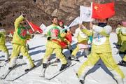 Werbung für Pekings Olympiabewerbung: Dort, wo 2022 die Bobwettbewerbe stattfinden sollen, versuchen chinesische Schüler schon einmal olympisches Flair zu vermitteln und das Logo der Bewerbung in Szene zu setzen. (Bild: AP/Ng Han Guan)