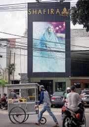 Strassenszene in Jakarta. Im Hintergrund das islamische Bekleidungsgeschäft Shafira. (Bild: Graham Crouch (Jakarta, 22. Januar 2018))
