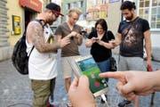 Patrick Bernecker (24), Simon Müller (23), Rahel Zoller (30), Jean-Luc Maréchaux (23, v. l.) und Phillip Party (23, hält das Handy in der Hand), spielen vor dem «Stadtkeller» in Luzern (links im Bild) Pokémon Go. (Bild Aleksandra Mladenovic)