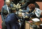 Gerangel im italienischen Senat, als ein Gegner des umstrittenen Gesetzes ein Plakat mit der Aufschrift «Stopp Invasion» in die Höhe hält. (Bild: Giuseppe Lami (15. Juni 2017, Rom))