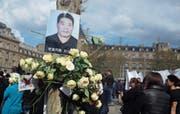 Ein Porträt des getöteten Chinesen während eines Protests gestern in Paris. (Bild: Thibault Camus/AP (Paris, 2. April 2017))