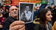 Während Selahattin Demirtas vor Gericht aussagt, hält ein Anhänger vor dem Gerichtsgebäude in Istanbul ein Bild des HDP-Chefs hoch. (Bild: Ozan Kose/AFP (12. Januar 2018))