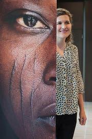 Jana Maletic neben einem Plakat am Caritas-Schweiz-Hauptsitz in Luzern. (Bild Boris Bürgisser)
