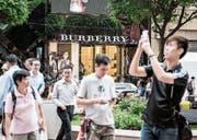 Passanten vor einem Burberry-Shop an einer Einkaufsstrasse in Hongkong. (Bild: Xaume Olleros/Getty (10. August 2015))
