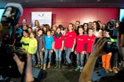 Schulkinder nehmen an der Verleihung des 1. Schulpreises die Bühne im Berner Stade de Suisse in Beschlag. Hinten links stehen die Moderatoren und Preisverleiher Fabian Cancellara und Christa Rigozzi. (Bild: Keystone/Peter Schneider)