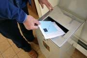 Ein Mann wirft einen Stimmzettel in eine Urne. (Symbolbild LZ)