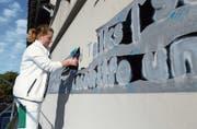 Die Malerin Andrea Brändli entfernt die Folie, hinter der verschiedene Begriffspaare erscheinen.