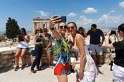 Gute Stimmung herrschte gestern bei Griechenland-Touristen vor dem Parthenon auf der Akropolis in Athen. (Bild: AP/Daniel Ochoa de Olza)