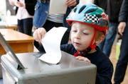 Noe Bouissoux aus Bern wirft den Abstimmungszettel seines Vaters in die Wahlurne. (Bild: Keystone / Peter Klaunzer)
