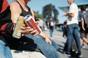 Jugendliche prosten sich auf einem öffentlichen Platz mit einem Bier zu. (Bild: Boris Bürgisser)