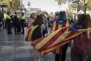 Eine Gruppe junger Menschen trägt die Flagge von Katalanien in Barcelona. (Bild: EPA/JIM HOLLANDER)