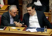 FILE - In this Friday, Feb. 24, 2017 file photo Greek Prime Minister Alexis Tsipras, right, speaks with the Deputy Prime Minister Giannis Dragasakis, during a Parliament session about bailout negotiations in Athens. Prime Minister Alexis Tsipras on Wednesday, Feb. 28, 2018 has appointed deputy premier Yannis Dragasakis as the country's economy and development minister in a limited cabinet reshuffle triggered by a rent allowance scandal. (AP Photo/Thanassis Stavrakis, File) (Bild: Thanassis Stavrakis / AP / Keystone (Athen, 24. Februar 2017))