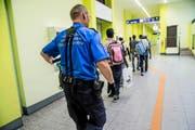 Ein Grenzwächter begleitete am Montag Migranten zur Personenkontrolle am Zoll des Bahnhofs Chiasso. (Bild: Keystone/Sara Solca)
