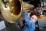 Fritz Müller in seinem Blasinstrumenten-Atelier an der Obergrundstrasse 44 mit einer Bass-Tuba, die er gerade mit einem kleinen Hammer ausbeult. (Bild Dominik Wunderli)