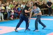 Die Zuschauer verfolgen, wie ein Polizist sich bei einem Angriff selbst verteidigt. (Bild: pd)
