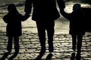 Eine Mutter geht mit ihren zwei kleinen Kindern spazieren. (Bild: Keystone / dapd)