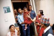 Die dreijährige Trishna Shakya wird von ihrem Vater zum Kloster gebracht. (Bild: Bikram Rai/Keystone (Kathmandu, 28. September 2017))
