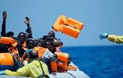 Bilder wie dieses sind in den letzten Monaten traurig vertraut geworden: Flüchtlinge im Mittelmeer vor der Küste Libyens. Hier rüsten Rettungskräfte eine Gruppe mit Schwimmwesten aus. (Bild: AP/Gregorio Borgia)
