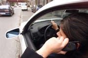 Rauchen und telefonieren im Auto führt zu Unaufmerksamkeit im Strassenverkehr (gestellte Szene). (Bild: Archiv Neue ZZ)