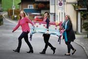 Kerstin Harris, Cornelia Rogenmoser und Tanja Kneringer (von links) von der Frauengemeinschaft Unterägeri mit einer Bank, die speziell für das Jubiläum entworfen wurde. (Bild: Stefan Kaiser (Unterägeri, 2. November 2017))