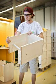 Der Zivildienstleistende Lars Troxler zeigt einen Ulmer Hocker, der in der Stiftung Brändi in Kriens produziert wird. (Bild Manuela Jans-Koch)