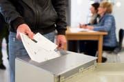 Ein Mann wirft seine Zettel in einem Wahlbüro in eine Urne. (Bild: Keystone / Gian Ehrenzeller)