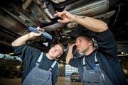 Mechatroniker-Lehrling Markus Häfliger (links) und Automechaniker Marcel Isenschmid kontrollieren in einer Werkstatt in Oberkirch einen Autoauspuff. (Bild: Dominik Wunderli/Neue LZ)