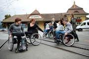 Angela Fallegger und Michelle Schönenberger (von links) schauen Tim Shelton vom Schweizer Paraplegiker-Zentrum zu, wie die Schienen der Zahnradbahn bei Vitznau zu überwinden sind. (Bild: Corinne Glanzman / Neue LZ)