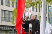 Gemeindepräsident Georges Helfenstein und Gemeinderat Markus Baumann gehen auf Tuchfühlung mit einer der neuen Fahnen. (Bild: Stefan Kaiser / Neue ZZ)
