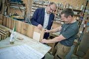 Karl Bucher (links) bespricht mit seinem Möbelschreiner Felix Bürgler einen Auftrag in der Werkstatt in Goldau. Eine Kontrolle im Rahmen des Gesamtarbeitsvertrags verursachte Bucher viel Bürokratie. (Bild Pius Amrein)