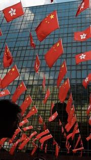 Die Fahnen von China und Hongkong wehen vor einem (Bild: Kin Cheung/AP (28. Juni 2017))