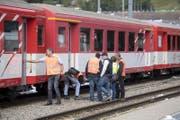 Experten untersuchen einen Wagen im Bahnhof Andermatt. (Bild: Urs Flüeler / Keystone (Andermatt, 11. September 2017))