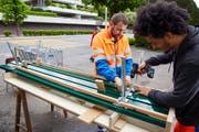 Benedikt Bucher, Leiter ReFit vom Strasseninspektorat Luzern, montiert zusammen mit einem Mitarbeiter eine Sitzbank. (Bild: Emanuel Ammon/pd)