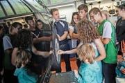 Der stellvertretende Werkstattleiter Gert Ruge erklärt Ferienpass-Kindern im Autohaus Imholz in Ebikon ein Auto. An der Führung nehmen auch Kinder mit Behinderung teil. (Bild Pius Amrein)