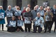 Betroffene von fürsorgerischen Massnahmen posieren anlässlich der Einreichung der Wiedergutmachungsinitiative mit alten Fotos vor dem Bundeshaus. (Bild: Lukas Lehmann/Keystone (Bern, 31. März 2014))