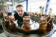 Maschinenführer Paul Mehr kontrolliert in der Diwisa-Fabrik in Willisau Flaschenverschlüsse. (Bild Philipp Schmidli/Neue LZ)