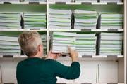 Eine Mitarbeiterin des Steueramts legt Steuererklärungen in einem Regal ab. (Bild: Christian Beutler / Keystone)