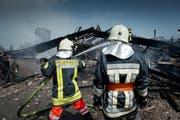 Damit im Brandfall genug Einsatzkräfte vor Ort sein können, braucht die Luzerner Feuerwehr wieder mehr Nachwuchs. Im Bild: Zwei Feuerwehrleute beim Löschen des Scheunen-Vollbrandes in Hasle von Ende Juli. (Bild: Pius Amrein / Neue LZ)