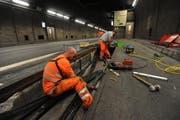 Zwei Mitarbeiter ziehen im Gotthard-Tunnel ein neues Kabel für das neue Videoüberwachungssystem ein. (Bild: Urs Hanhart)